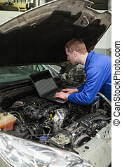 Mechanic using laptop on car engine