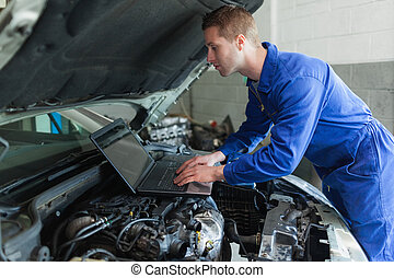 Auto mechanic working on laptop