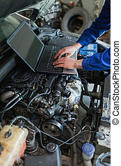 Mechanic hands using laptop on car engine