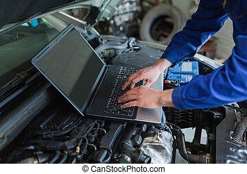 Auto mechanic using laptop - Close-up of auto mechanic using...