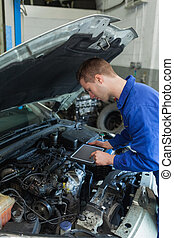 Car mechanic using tablet computer - Car mechanic by car...