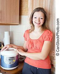 Woman with electric crock pot in  kitchen at home