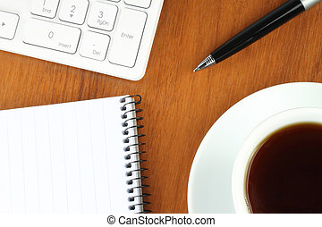 Keyboard, coffee, notepad and pen on wooden background