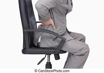 Business man with backache sitting in an office chair - Side...