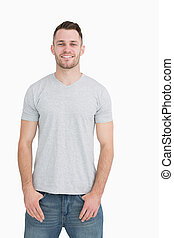 Portrait of casual smiling young man standing over white...
