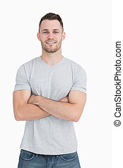 Portrait of casual young man standing with arms crossed over...