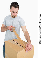 Man sealing cardboard box with packing tape - Young man...