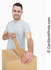 Portrait of man sealing cardboard box with packing tape -...