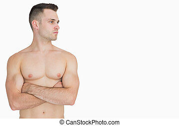 Bare chested man with arms crossed looking to his side -...