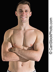 Portrait of bare chested young man with arms crossed over...