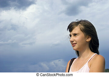 Young girl look forward on sky background