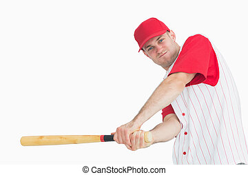 Portrait of young baseball player swinging bat over white...