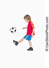 Side view of little boy kicking football over white...