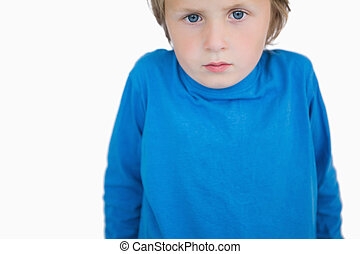 Portrait of cute young boy standing over white background