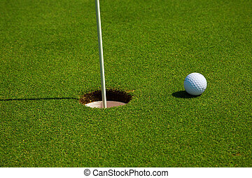 Golf ball in a course and hole. Golf green.