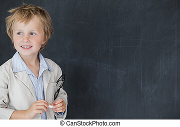 Boy dressed as teacher standing in front of black board -...