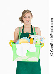 Portrait of young maid carrying cleaning supplies over white...