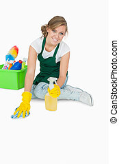 Portrait of young maid cleaning floor over white background