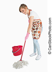 Young maid mopping floor over white background