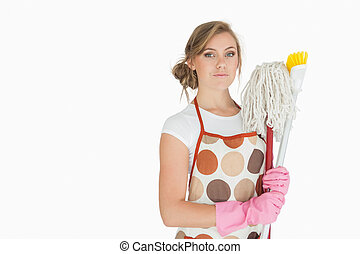 Portrait of young woman with cleaning supplies over white...