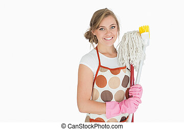 Portrait of smiling woman with cleaning supplies - Portrait...