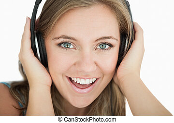 Close-up of young woman listening music through headphones...