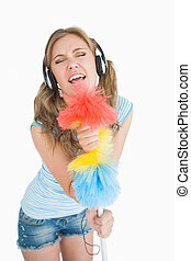 Woman holding feather duster as mic - Woman holding feather...