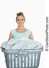 Portrait of smiling woman carrying laundry basket - Portrait...