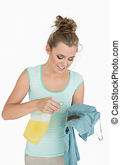 Young woman with spray bottle and stained shirt over white...