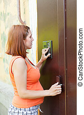 pregnant woman using house intercom outdoor