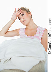 Tired young woman with stack of clothes