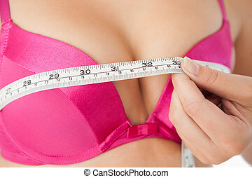 Woman measuring chest in pink bra - Extreme close-up of...