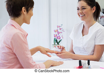 Happy young manicurist using nail brush on woman's nails in...