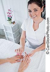 Portrait of manicurist filing woman's nails - Portrait of...