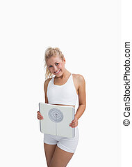Portrait of young happy woman holding weighing scales over...