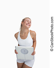 Excited young happy woman holding weighing scales over white...
