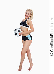 Portrait of happy woman in sportswear holding football over...