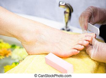 Close-up of nail technician filing woman's toe nails at nail...