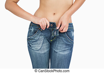 Midsection of slim woman buttoning jeans over white...