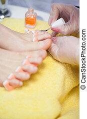 Close-up of woman applying nail varnish to toe nails