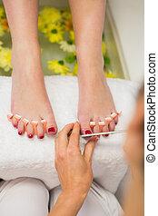 Woman polishing toe nails at spa center