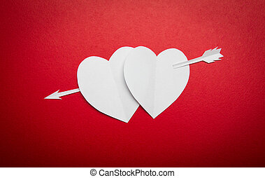 Two paper hearts pierced with an arrow symbol for Valentines...