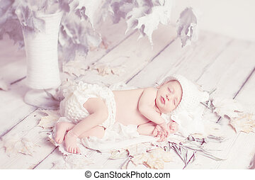 Newborn baby sleeping on leaves over white wooden background