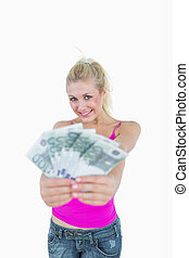 Portrait of happy young woman holding fanned euro banknotes...