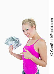 Portrait of happy woman pointing at fanned euro banknotes...