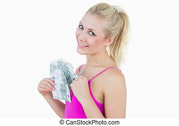 Portrait of happy woman with fanned euro banknotes over...