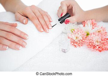 Woman applying nail varnish to finger nails - Close-up of...