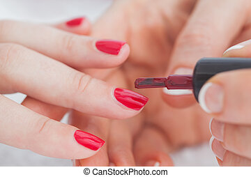 Details shot of hands applying red nail varnish to nails -...