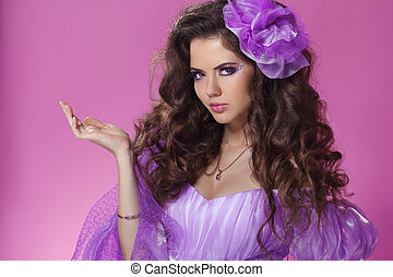 Beautiful woman with long curly hair style over purple