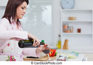 Young woman pouring wine while preparing food